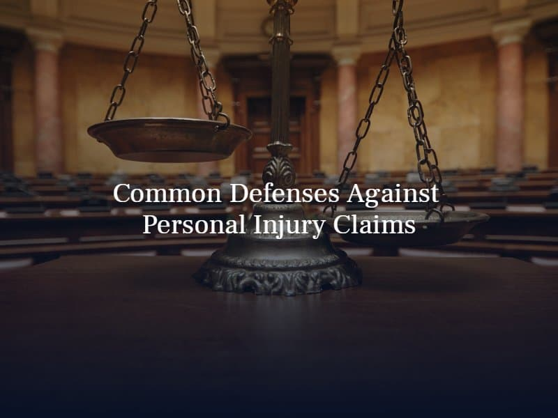 """legal scale in an empty courtroom. Text: """"Common Defenses Against Personal Injury Claims"""""""
