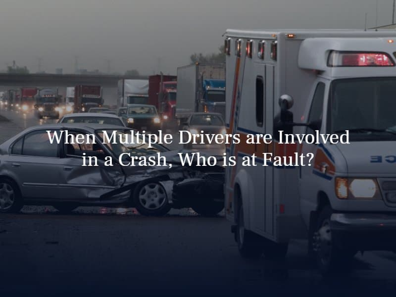 """ambulance parked in front of a smashed sedan on a busy road with cars and trucks coming. text: """"When multiple drivers are involved in a crash, who is at fault?"""""""