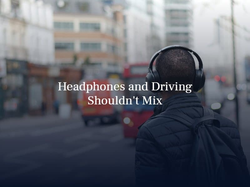man wearing headphones standing on the sidewalk | text: headphones and driving shouldn't mix